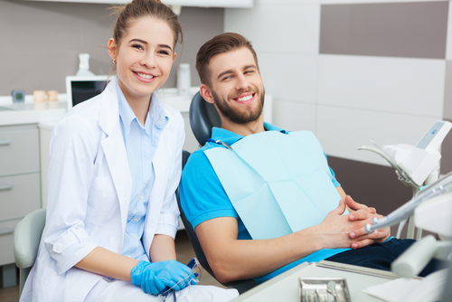 young male patient and female dentist smiling