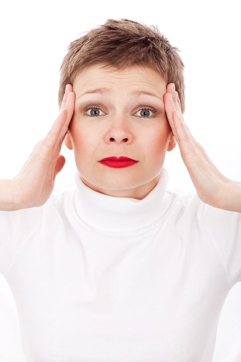 middle-aged woman holding both sides of her head from a migraine