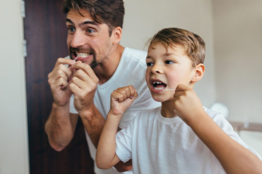 Father and son flossing in the mirror together