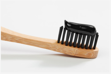 wooden toothbrush with charcoal toothpaste on it