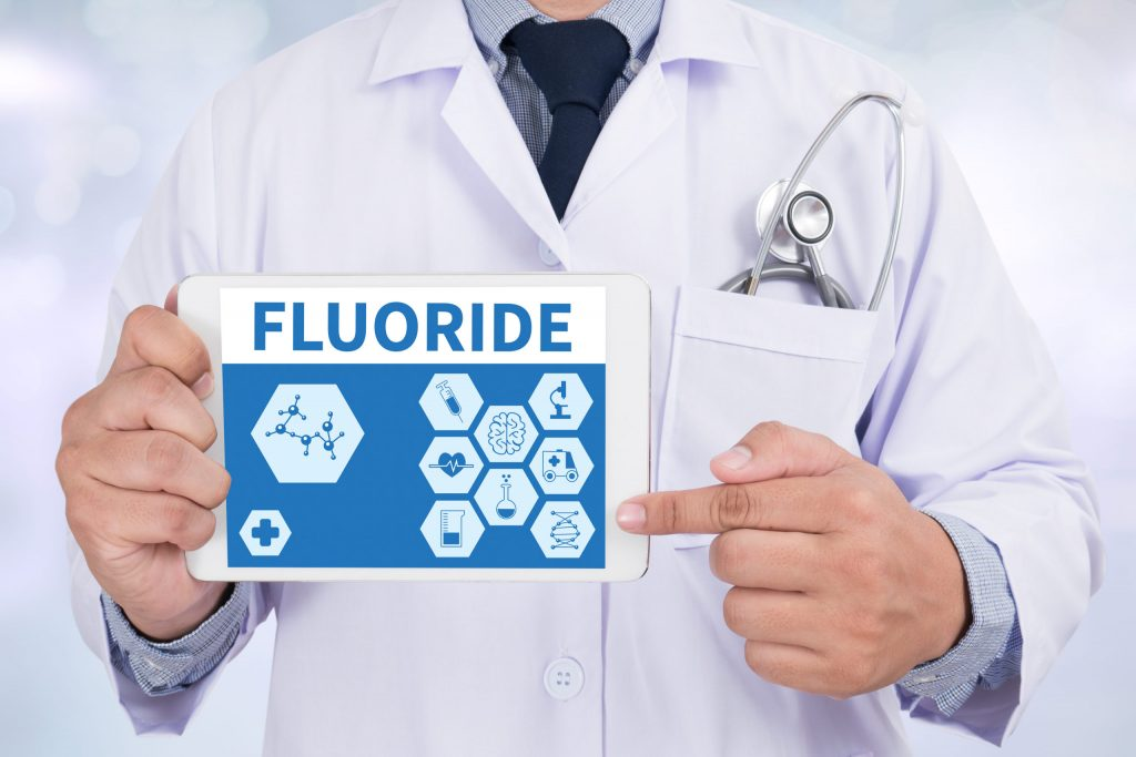 dentist holding up a tablet with fluoride information